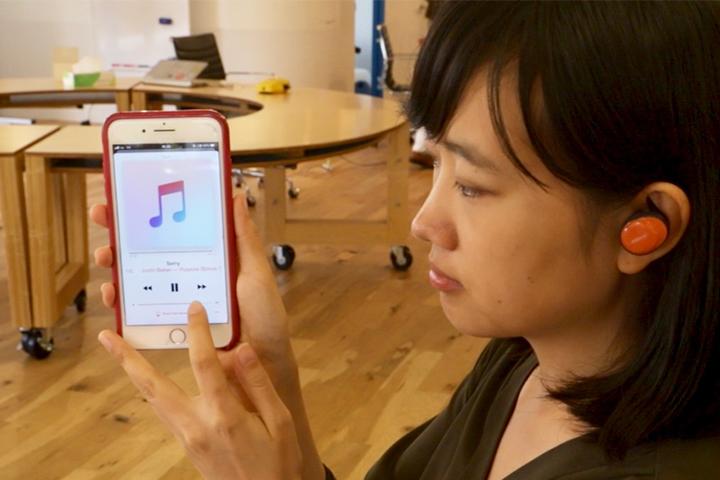 iphoneのミュージック画面と聞いているひとをうしろからのアングルで