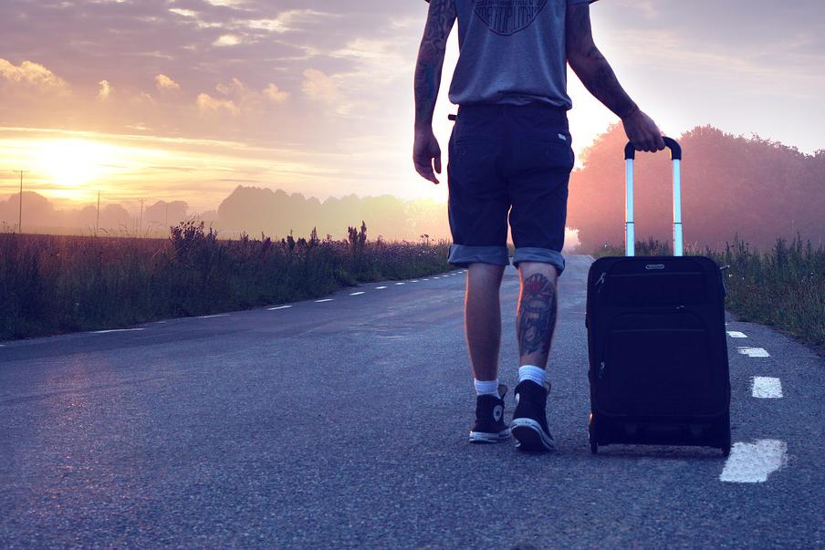 スーツケースを持って歩く男性