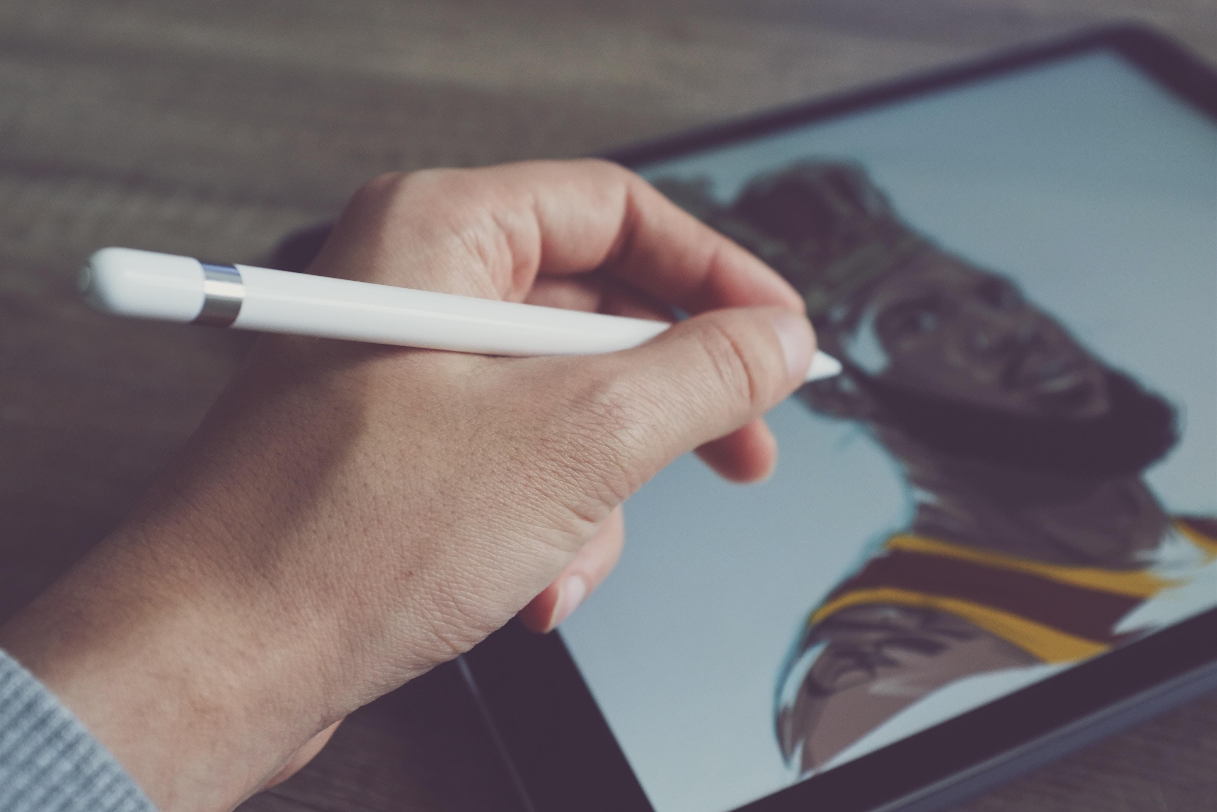 液晶タイプのペンタブで絵を描いている人の手の写真