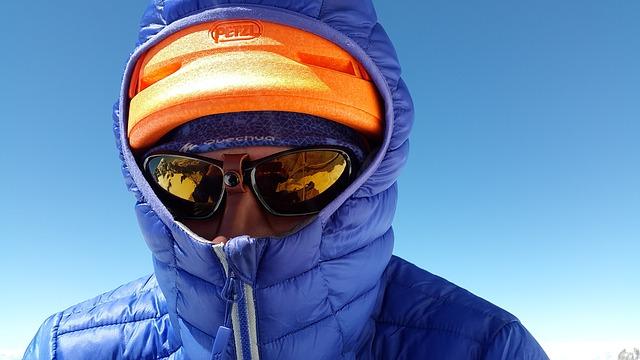 ダウンジャケットを着て寒さをしのいでいる男性の写真