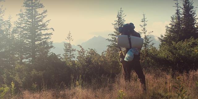寝袋を持って登山している人の写真