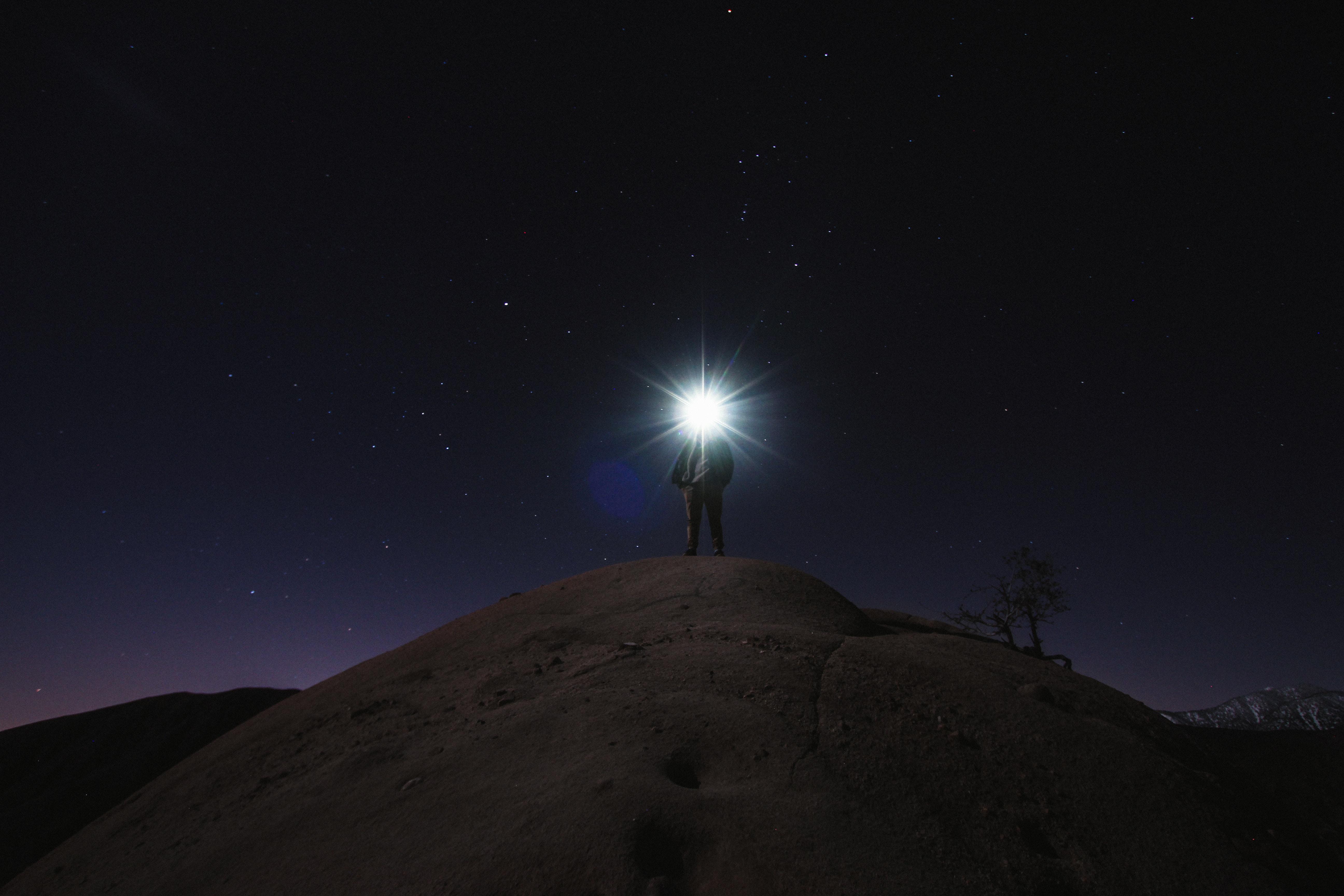 山頂でライトを持つ男性