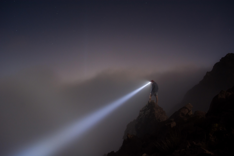 霧の中をライトで照らす人