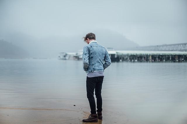 冬の水辺に佇む男性