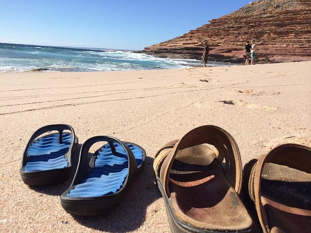 海辺に置かれているサンダルの写真