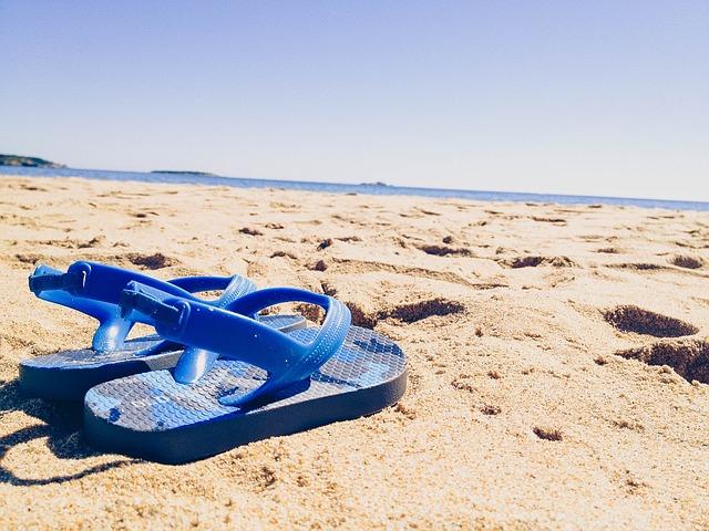 砂浜の上に置かれているサンダルの写真