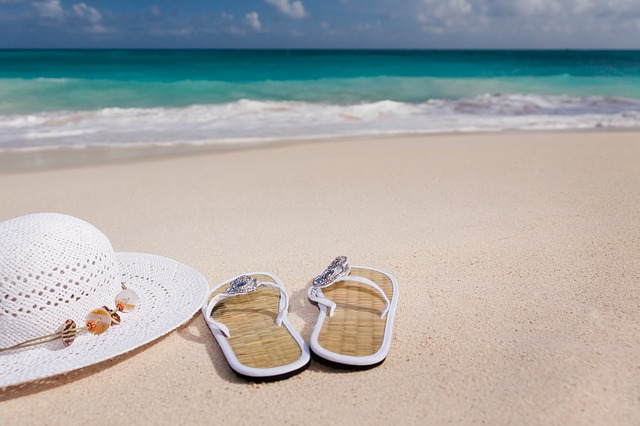 砂浜のサンダルと帽子
