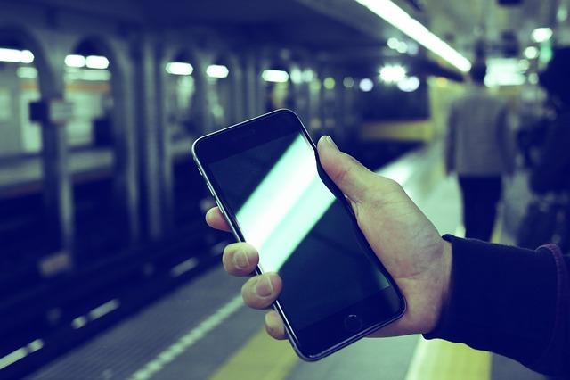 駅のホームでスマホを持っている人の写真