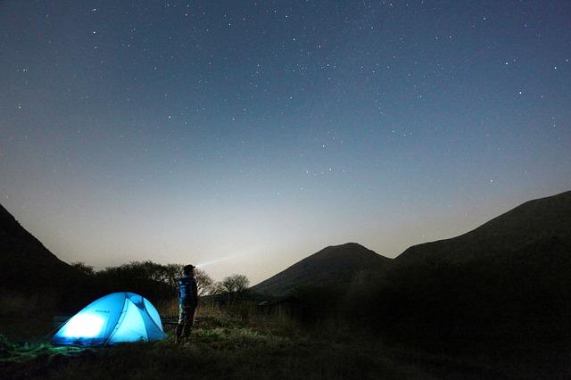 テントの横で夜空を見上げている男性の写真