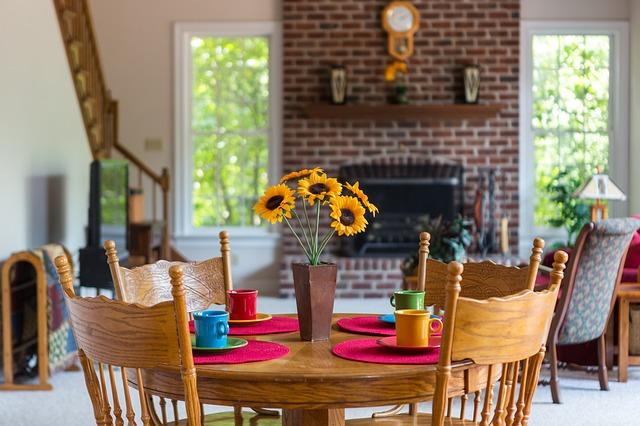 カップや花が置かれた円形のダイニングテーブル
