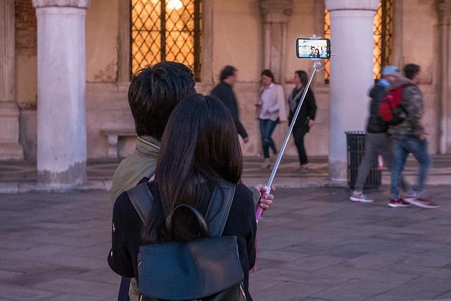 男の人と女の人が自撮り棒を使って撮影している時の写真