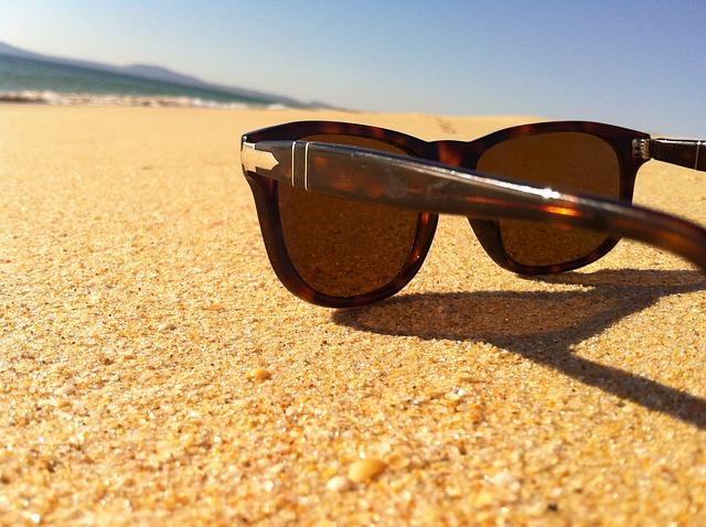 砂浜に置いてあるサングラスの写真