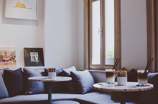 ソファの近くにあるテーブルの上にコーヒーが置かれている写真