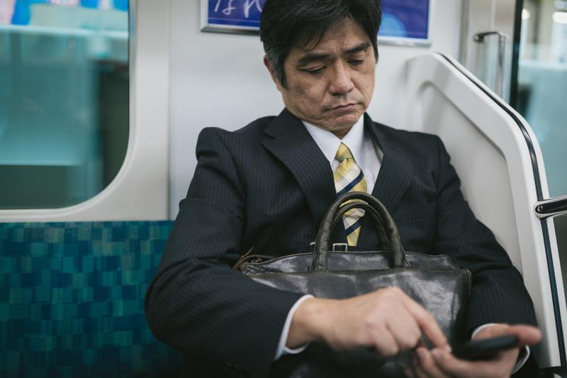 通勤中にスマホを見る男性