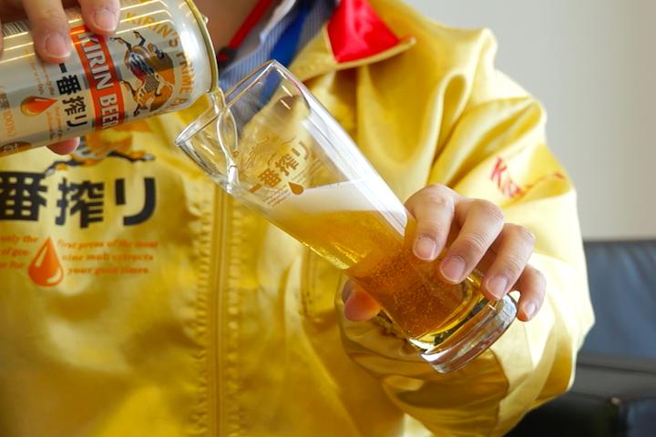 グラスを45度に傾けてビールを注ぐ写真