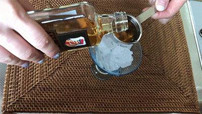氷の入ったグラスにウィスキーを注ぐ様子