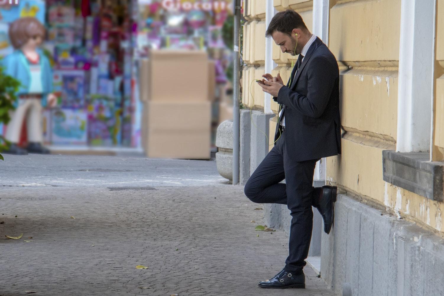 屋外で壁にもたれかかりながらiPhoneをいじる男性