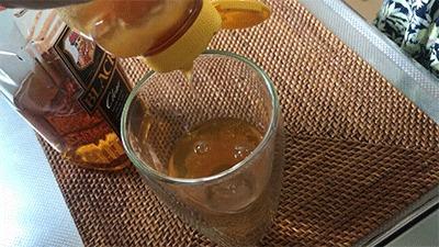 ウイスキーのお湯割りにはちみつを足す様子