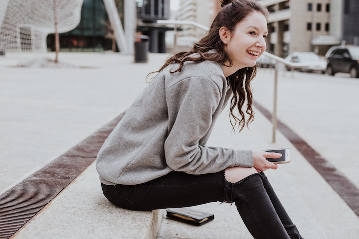 iPhoneを手に持つ笑顔の女性
