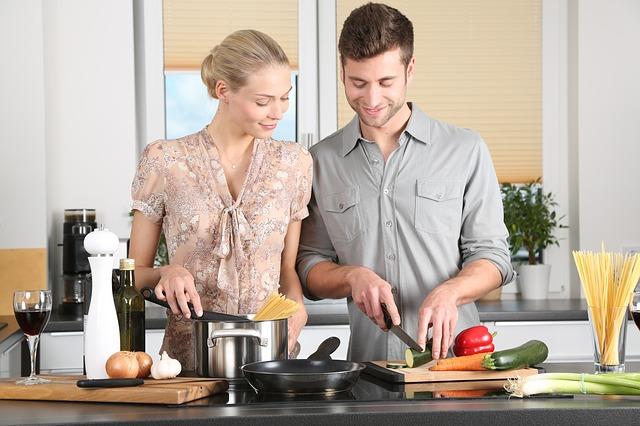 二人で料理をする男女の画像