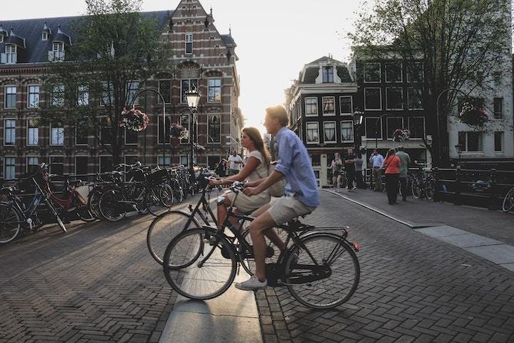 自転車で街中を走行する男女
