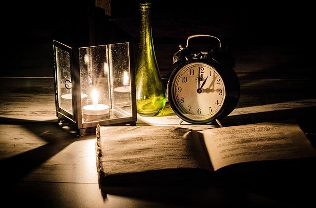 テーブルの上の時計と本の写真