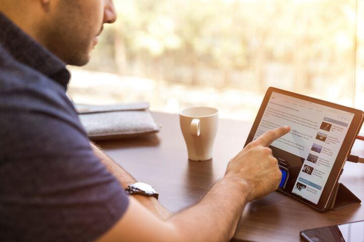 テーブルに置いたiPadを操作する男性