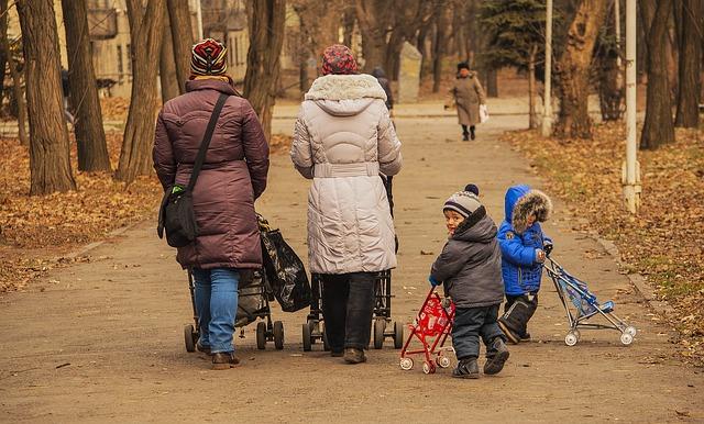 親子が公園でベビーカーを押している写真