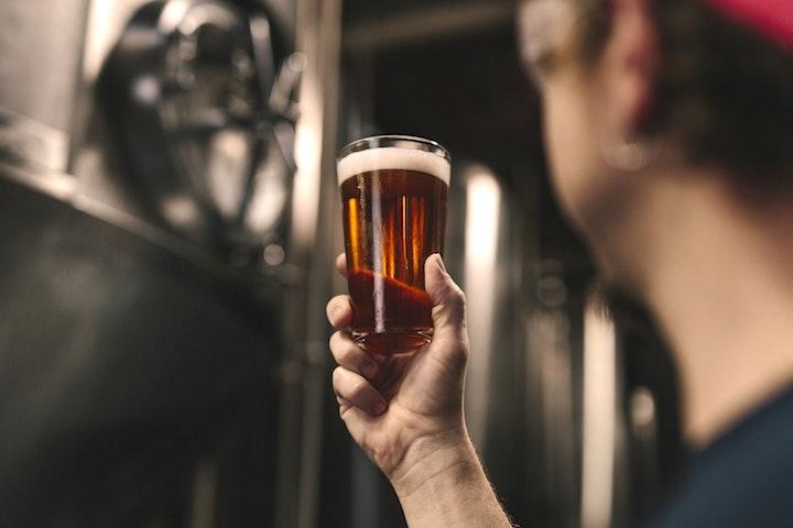 グラスに入ったビールを見つめる男性