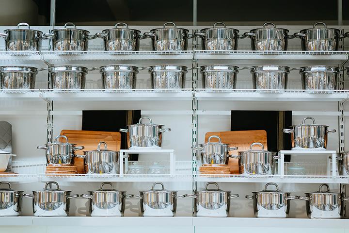 ステンレス鍋が並んだキッチンキャビネット