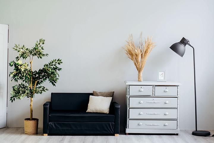 シンプルなフロアライトと黒いソファのあるリビング