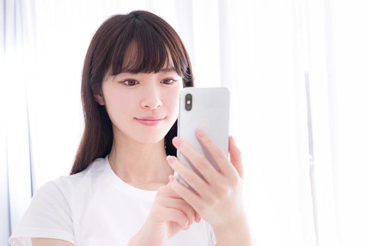 スマートフォンで検索する女性の写真